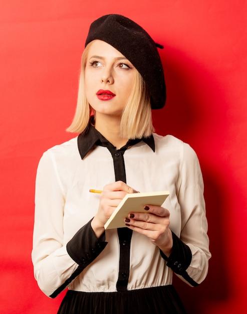 De mooie franse vrouw in baret houdt notitieboekje met potlood op rode muur Premium Foto
