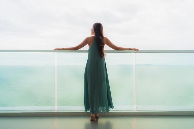 De mooie gelukkige glimlach van de portret jonge aziatische vrouw ontspant bij balkon met overzeese oceaan Gratis Foto