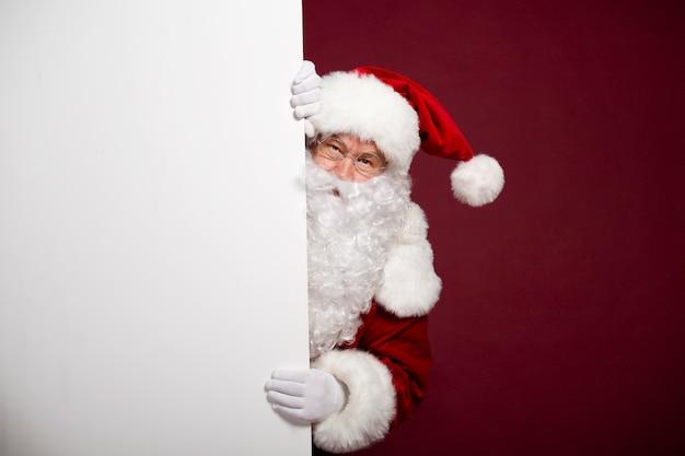 De mooie gelukkige opgewekte kerstman stelt en toont wit leeg bord in handen Premium Foto