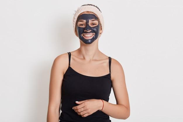 De mooie glimlachende vrouw met zwart klei gezichtsmasker op gezicht die zich tegen witte muur met charmante glimlach bevinden, leuk meisje die kosmetische procedures thuis doen, kijkt gelukkig. Gratis Foto