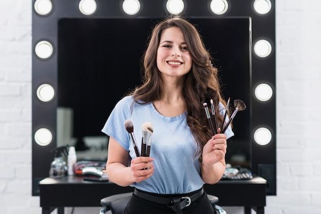 De mooie glimlachende vrouw van de make-upkunstenaar met borstels in handen Gratis Foto