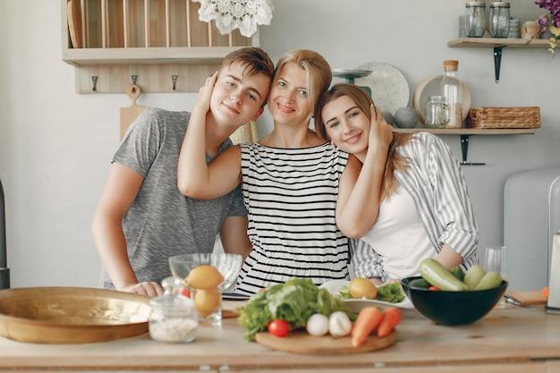 De mooie grote familie bereidt voedsel in een keuken voor Gratis Foto