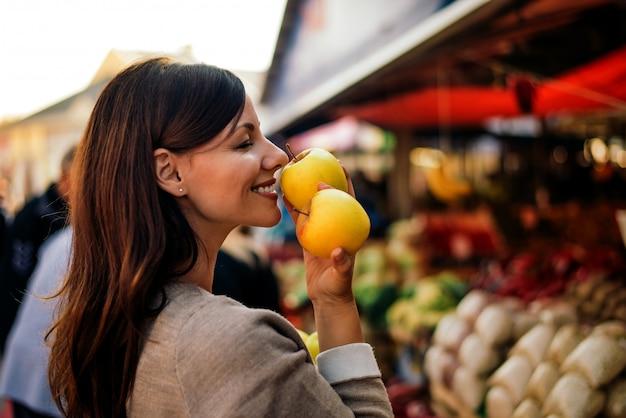 De mooie jonge appel van de vrouwenholding en het ruiken Premium Foto