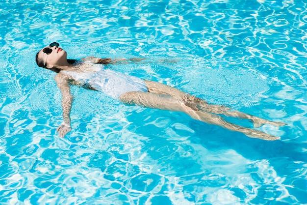 De mooie jonge aziatische gelukkige vrouw en de glimlach in zwembad voor ontspannen reis en vakantie Gratis Foto