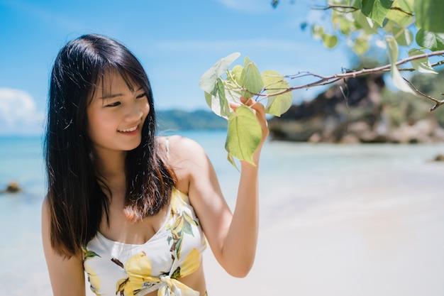 De mooie jonge aziatische gelukkige vrouw ontspant lopend op strand dichtbij overzees. Gratis Foto