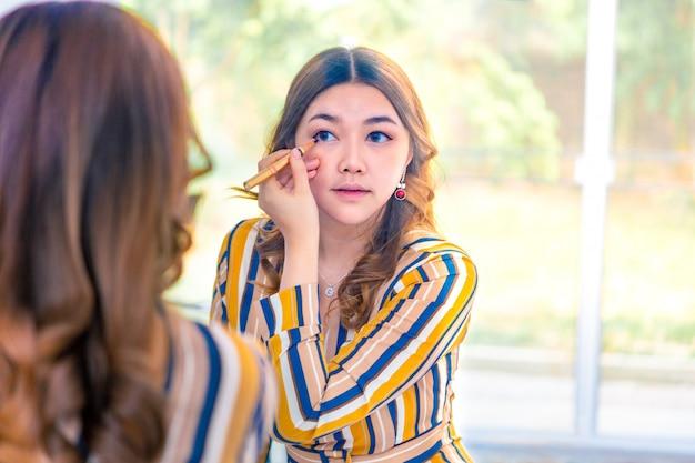 De mooie jonge aziatische vrouw die op haar zetten maakt omhoog voor haar groter slaapkamervenster Premium Foto