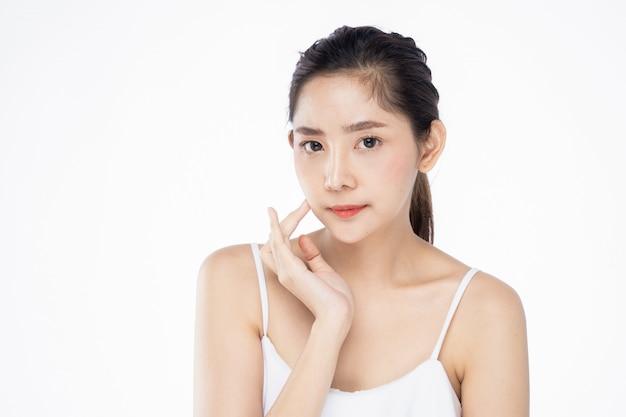 De mooie jonge aziatische vrouw met schone verse witte huid wat betreft haar eigen gezicht zacht in schoonheid stelt. Premium Foto