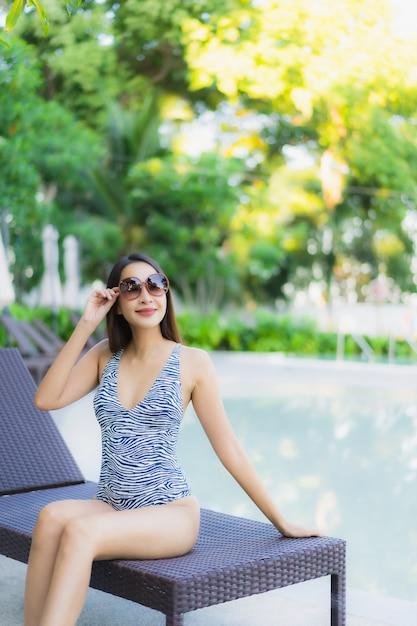De mooie jonge aziatische vrouwen gelukkige glimlach ontspant rond openluchtzwembad in hoteltoevlucht Gratis Foto