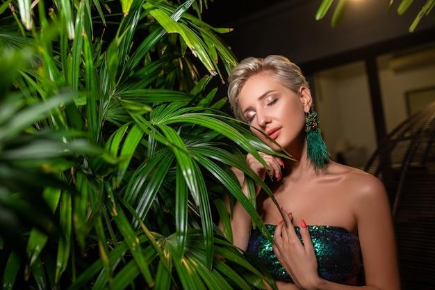 De mooie jonge blondevrouw met perfecte huid en lang lichtblond haar stelt op de aard Premium Foto