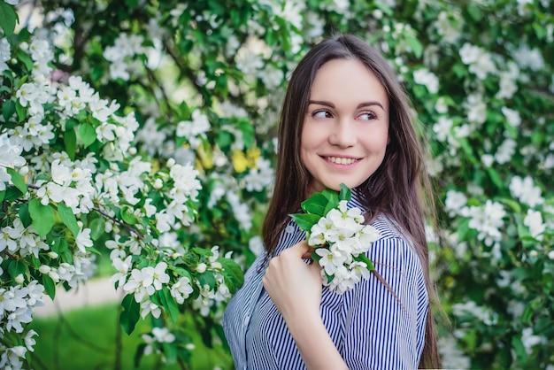 De mooie jonge bomen van de meisjes dichtbij bloeiende appel in de lente Premium Foto