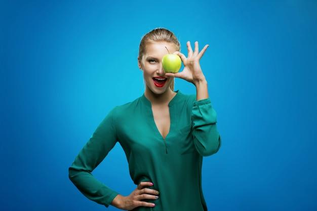 De mooie jonge gelukkige de glimlach van de geschiktheidsvrouw houdt groene appel. gezonde levensstijlfoto die op blauwe muur wordt geïsoleerd Premium Foto
