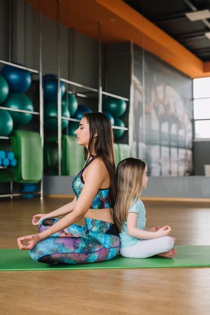De mooie jonge moeder en haar dochter mediteren terwijl het zitten in yoga stelt Gratis Foto