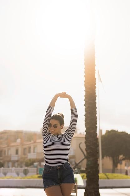 De mooie jonge vrouw die zonnebril dragen die haar uitrekken dient tuin in Gratis Foto