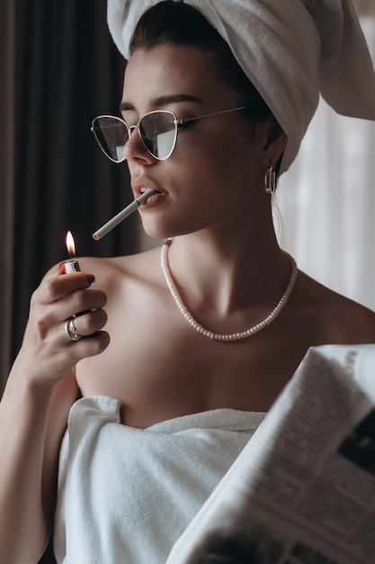 De mooie jonge vrouw in een handdoek rookt een sigaret en leest krant Gratis Foto