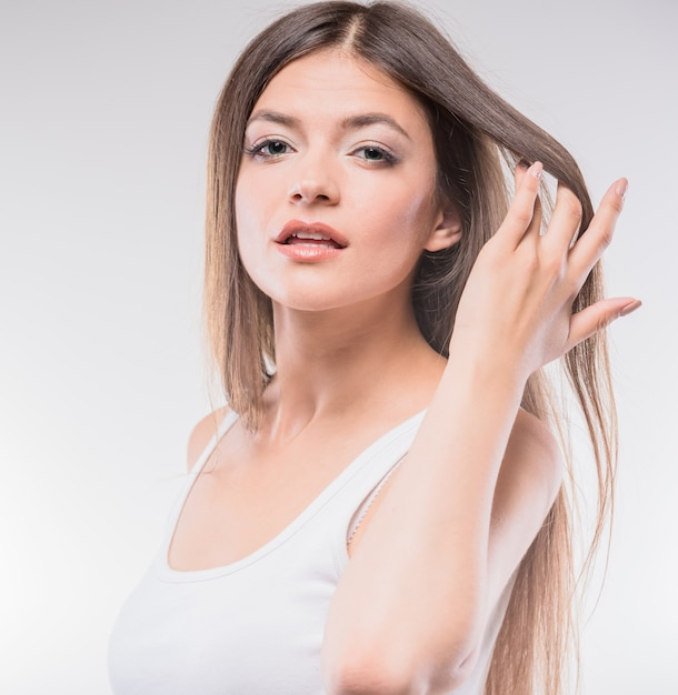 De mooie jonge vrouw in mouwloos onderhemdholding dient haar in. Premium Foto