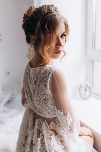 De mooie jonge vrouw in witte lingerie stelt in witte zijdebadjas in heldere hotelruimte Gratis Foto