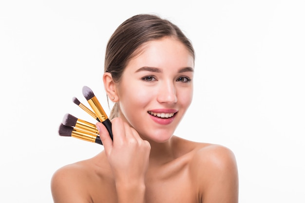 De mooie jonge vrouw met make-up borstelt dichtbij haar gezicht dat op witte muur wordt geïsoleerd Gratis Foto