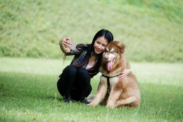 De mooie jonge vrouw vangt in openlucht foto met haar kleine hond in een park. levensstijl portret. Gratis Foto