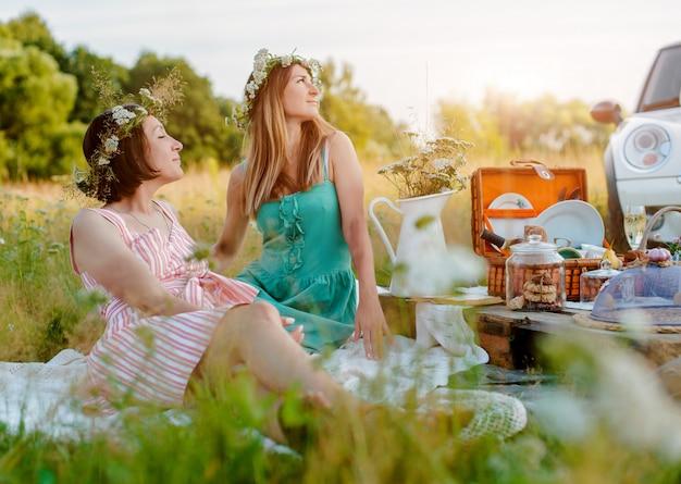 De mooie jonge vrouwen van meisjesmeisjes op een picknick in de zomerpret om wijn te vieren en te drinken. Premium Foto