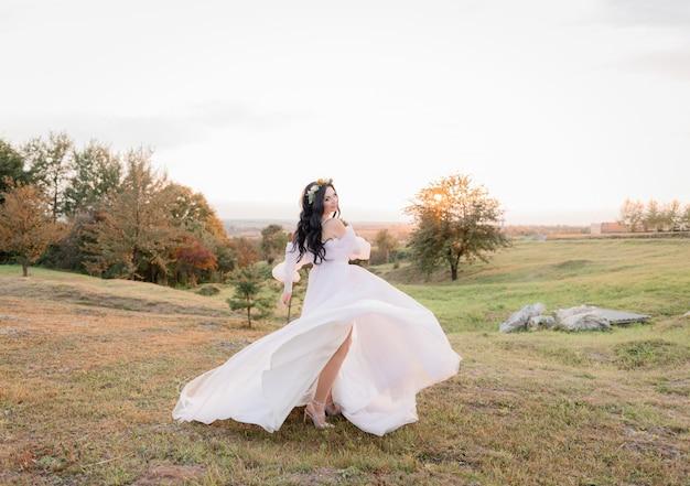 De mooie kaukasische donkerbruine bruid danst op de vergeelde weide in de warme de herfstavond Gratis Foto