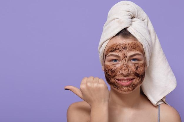 De mooie ontspannen glimlachende vrouwelijke puntenduimvinger op vrije ruimte, past natuurlijk chocolademasker op haar gezicht toe Gratis Foto