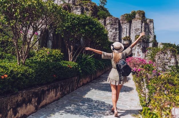 De mooie opgewekte blondevrouw backpacker loopt en bewondert tropische landschappen bij het hotel van het paradijseiland in sanya, china. achteraanzicht Premium Foto