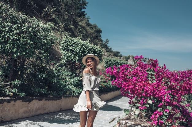 De mooie opgewekte blondevrouw loopt en bewondert tropische landschappen bij het hotel van het paradijseiland in sanya, china. Premium Foto