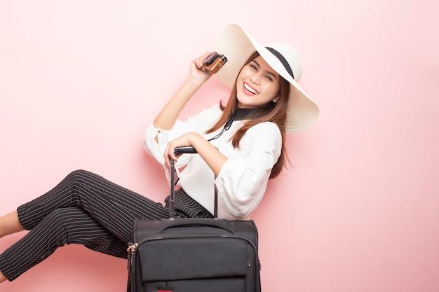 De mooie reizigersvrouw is opwindend op roze achtergrond Premium Foto