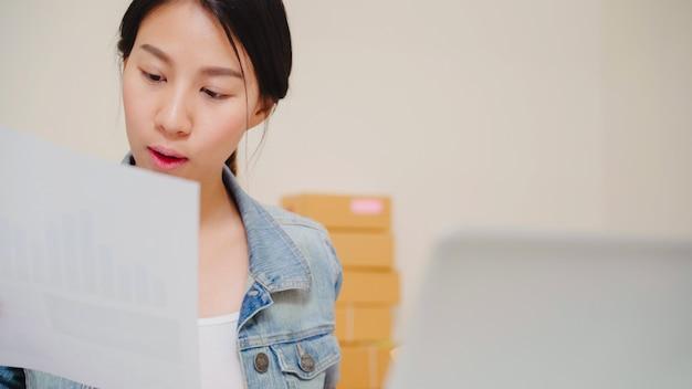De mooie slimme aziatische jonge ondernemer van de ondernemers bedrijfsvrouw van online het controleren van het mkb product op voorraad en sparen aan computer die thuis werken. Gratis Foto