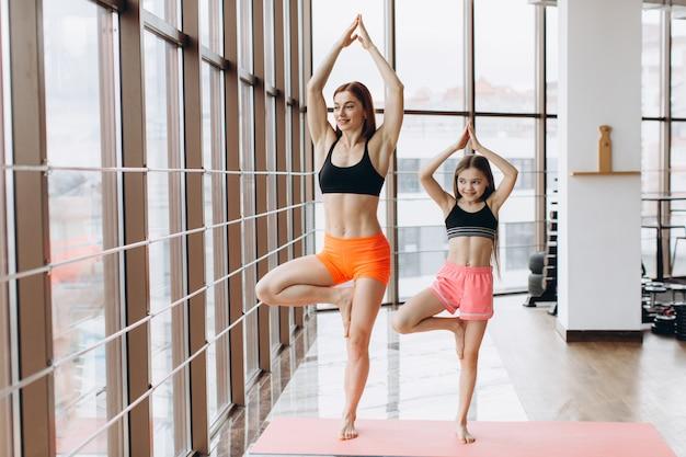 De mooie spiervrouw en haar charmant dochtertje glimlachen terwijl samen het doen van yoga bij gymnastiek Premium Foto