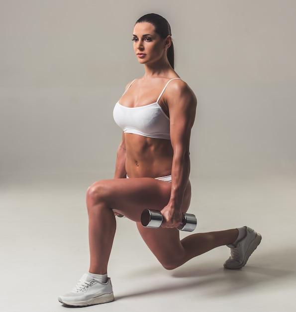 De mooie sterke vrouw in wit ondergoed doet lunges. Premium Foto