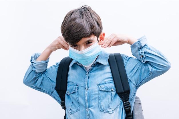 De mooie student van de kindjongen met rugzak en de boeken van de maskerholding op witte achtergrond Premium Foto