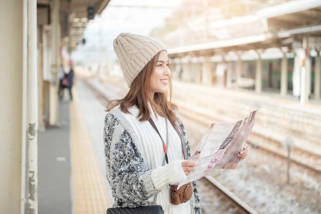 De mooie toeristenvrouw bevindt zich op spoorwegplatform met haar kaart Premium Foto