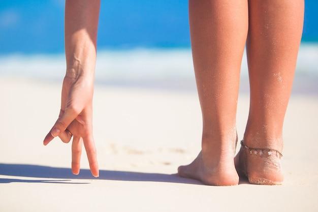 De mooie vlotte benen van vrouwen op wit zandstrand Premium Foto