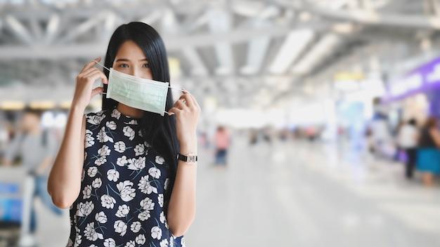 De mooie vrouw die een medisch masker dragen en zich over vage internationale airportliving bevinden met verhindert concept. Premium Foto