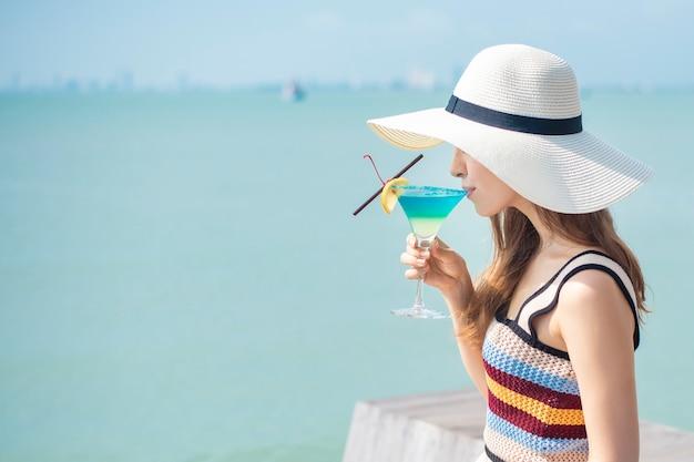 De mooie vrouw drinkt de drank van de ijszomer in het strand, de zomerconcept Premium Foto