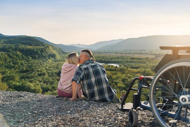 De mooie vrouw en haar wilsonbekwame echtgenoot zitten naast zijn rolstoel op de heuvel en kussen zachtjes. Premium Foto