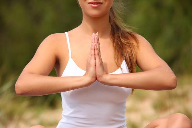 De mooie vrouw geniet van yoga bij bos Gratis Foto