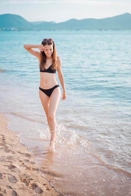 De mooie vrouw in zwarte bikini loopt van overzees, de zomerconcept Premium Foto