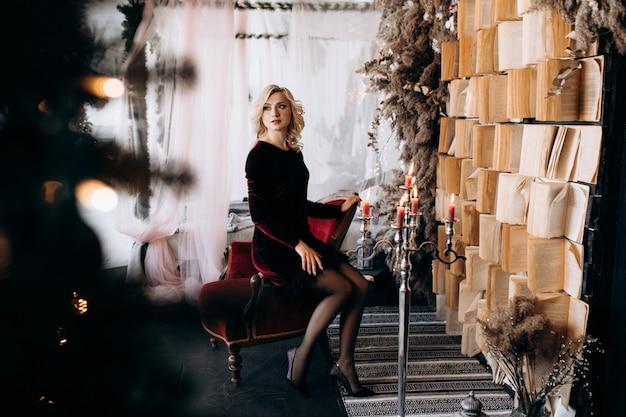 De mooie vrouw in zwarte kleding zit vóór een muur van boeken en kerstmisdecor Gratis Foto