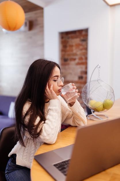 De mooie vrouw met lond zwart haar werkt aan haar laptop en drinkwater op de keuken Gratis Foto