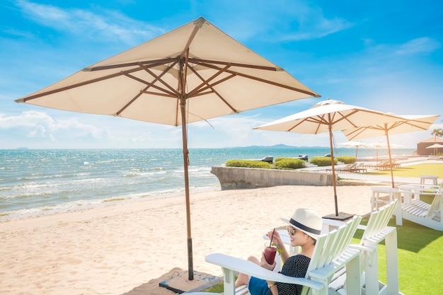 De mooie vrouw ontspant op het strand, onder paraplu Premium Foto
