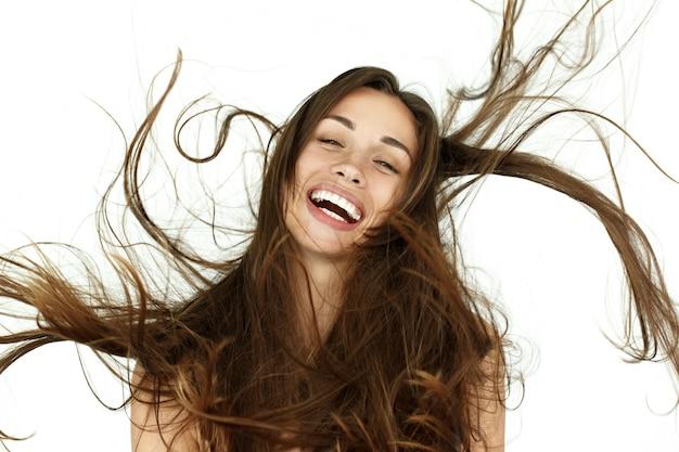 De mooie vrouw schudt haar haar op witte achtergrond Gratis Foto