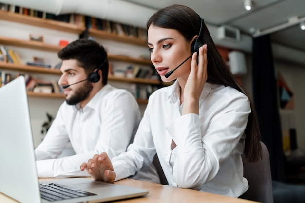 De mooie vrouw werkt in call centre met hoofdtelefoon die cliënttelefoongesprekken beantwoordt Premium Foto