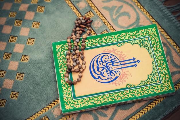 De moslimfoto met een oude rozenkrans en gebedenboek op de groene mat Premium Foto