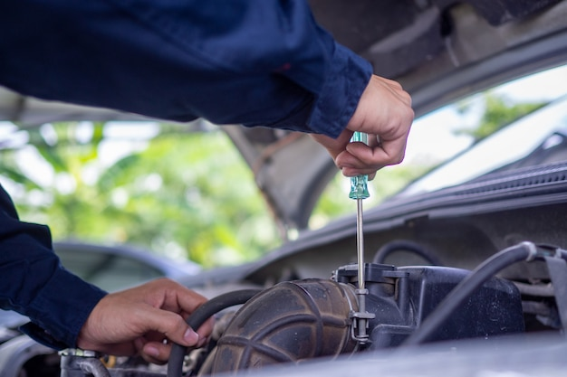 De motoringenieur controleert en repareert de auto. off-site zorgdiensten Premium Foto