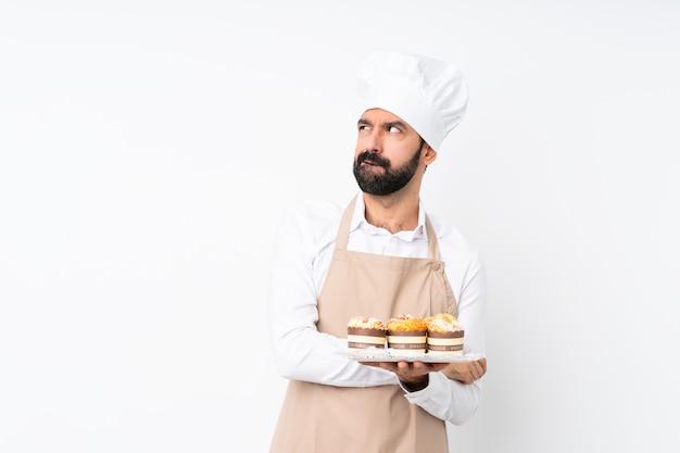 De muffincake van de jonge mensenholding over geïsoleerd wit met verwart gezichtsuitdrukking Premium Foto