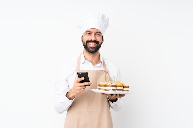 De muffincake van de jonge mensenholding over geïsoleerde witte muur die een bericht met mobiel verzenden Premium Foto