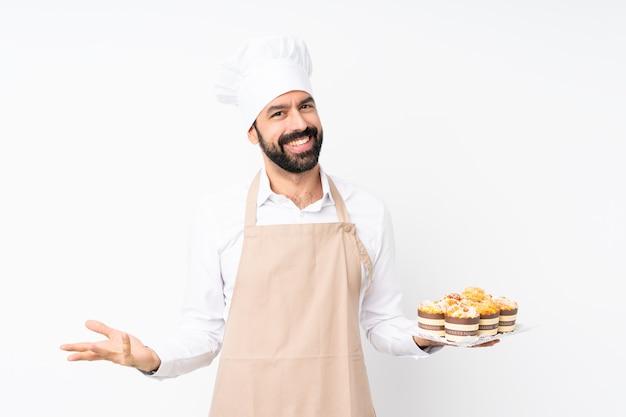 De muffincake van de jonge mensenholding over het geïsoleerde witte glimlachen Premium Foto