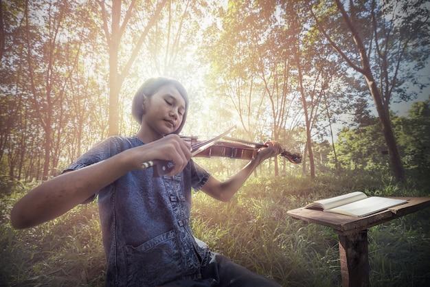 De musical: klein aziatisch kind dat viool speelt in de open lucht Premium Foto
